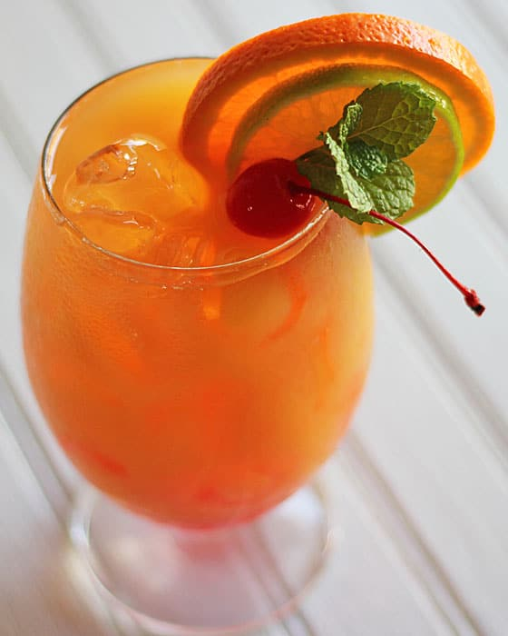Closeup of an orange cocktail with an orange slice, lime, mint and a cherry.