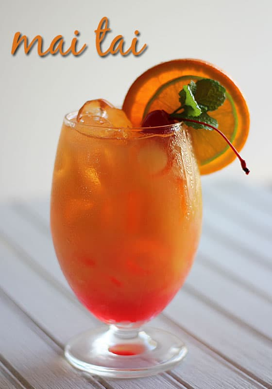 An orange cocktail in a glass garnished with an orange slice, lime, mint and a cherry. Text at top of image.