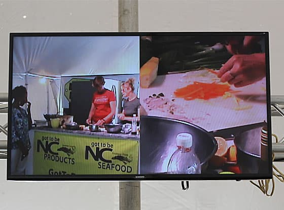 A wide screen monitor displaying a chef cooking and closeup of slicing vegetables.