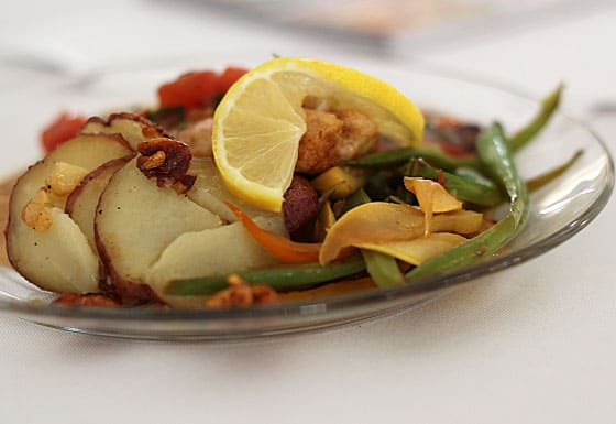 A closeup of trout with potatoes and green beans on a clear glass plate.
