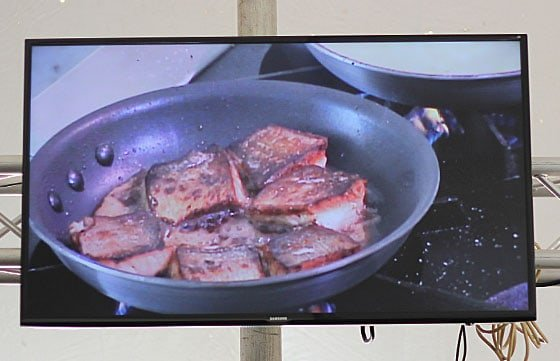 A wide screen monitor displaying fish frying in a pan.