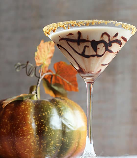 A martini in a glass that has been drizzled with chocolate syrup with a crushed cookie rim. A pumpkin is in background.
