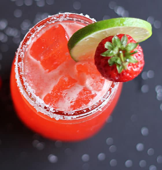 Overhead view of a margarita in a mason jar garnished with strawberry and lime.