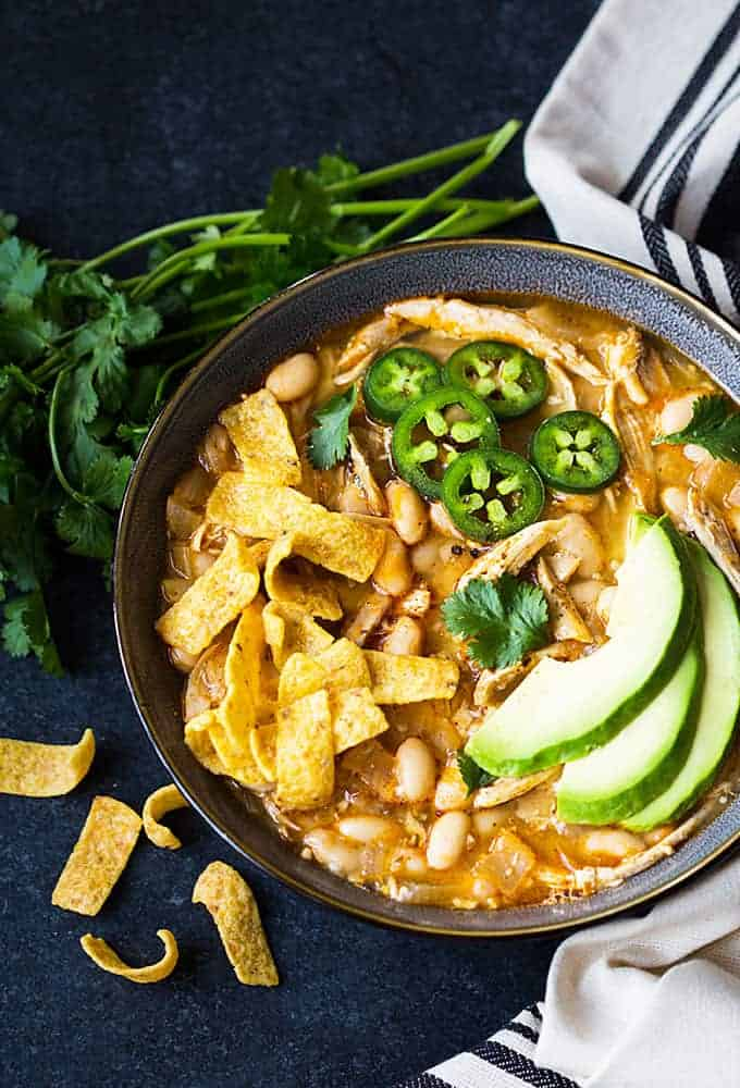 Overhead view of a bowl of chicken chili topped with avocado, chips and sliced jalapenos.
