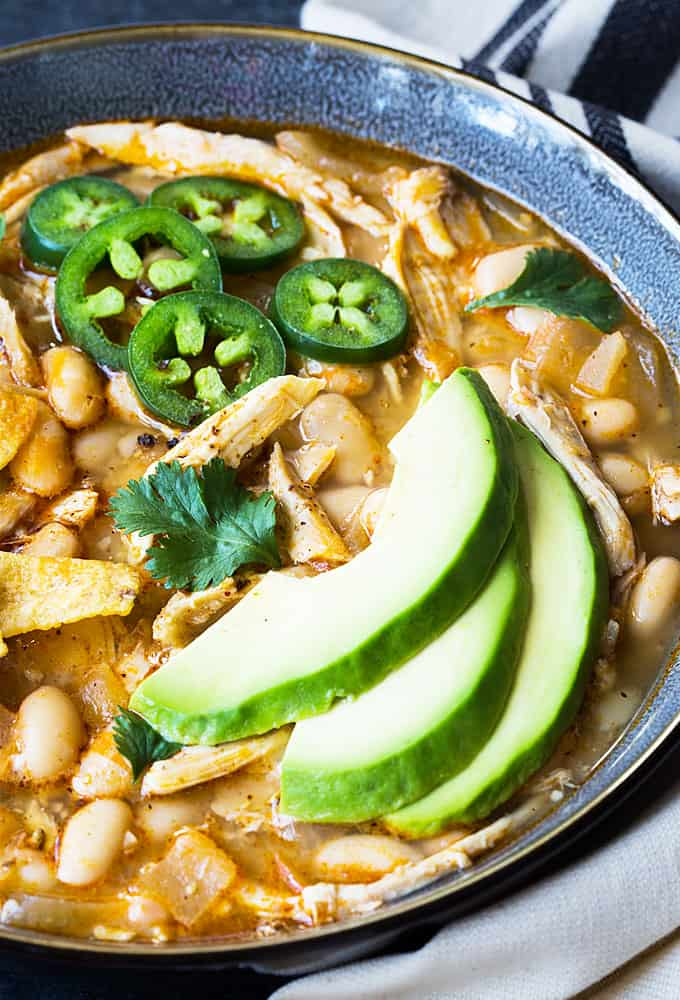 Closeup view of a blue bowl of chicken chili with avocado, jalapeno and corn chips.