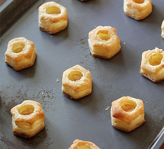 Baked puff pastry puffs on a baking sheet.