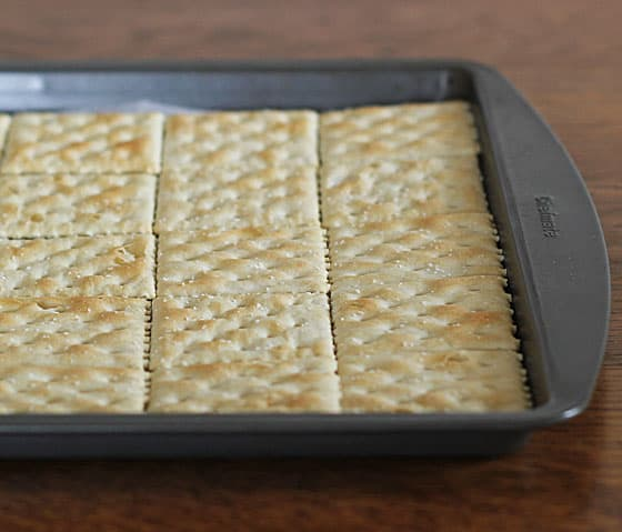 A baking sheet with saltine crackers arranged on it.