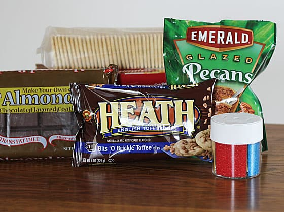 Packages of chocolate squares, saltine crackers, pecans, toffee and a container of decorative sprinkles.