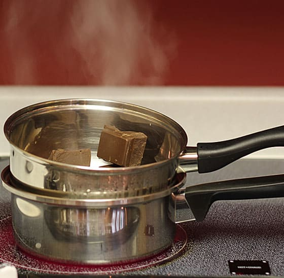 A double boiler on a stove burner melting chocolate squares.