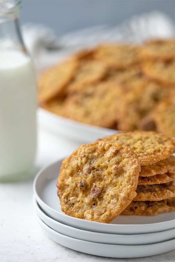 A stack of oatmeal lace cookies on a small round white plate