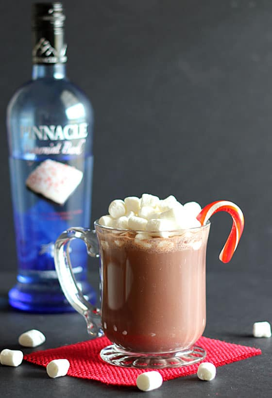 A mug of hot chocolate topped with marshmallows with a candy cane.  A blue bottle of vodka is in background.
