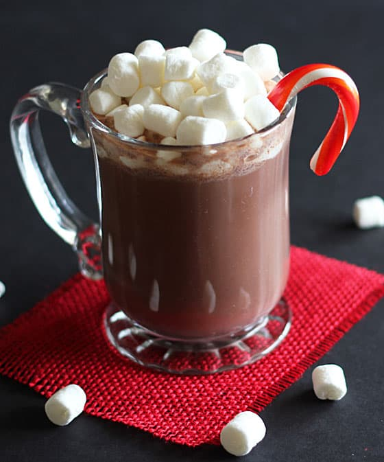A mug of chocolate cocktail with marshmallows and a candy cane on a square of red burlap.