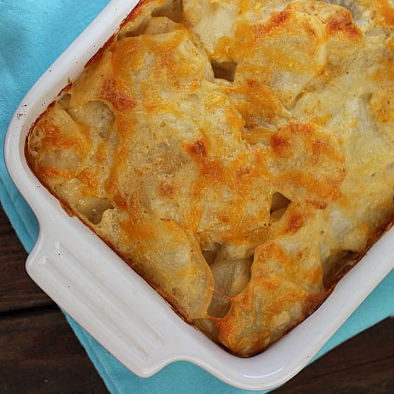 Overhead view of skinny scalloped potatoes in a white baking dish.