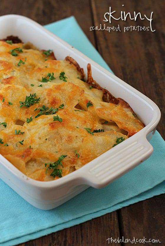 Scalloped potatoes in a white baking dish on a blue napkin.