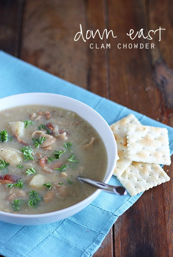 Clam chowder in a white bowl with a spoon on a blue napkin with saltine crackers. Text at top of image.