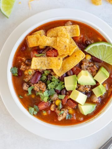 A white bowl of taco soup with corn chips, avocado and a lime wedge.