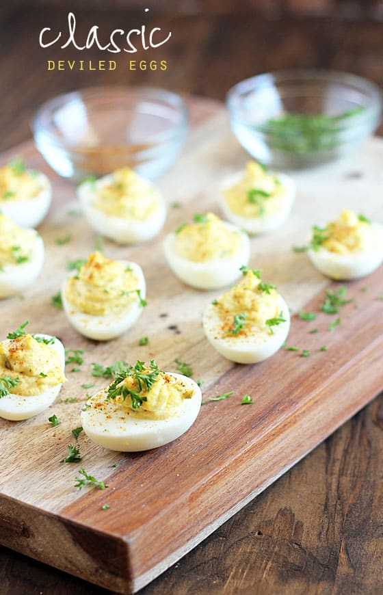 Deviled eggs garnished with parsley on a wooden cutting board. Text at top of image.