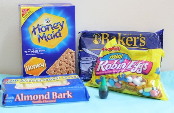A box of graham crackers, packages of coconut, robin eggs and chocolate and a bottle of food coloring.