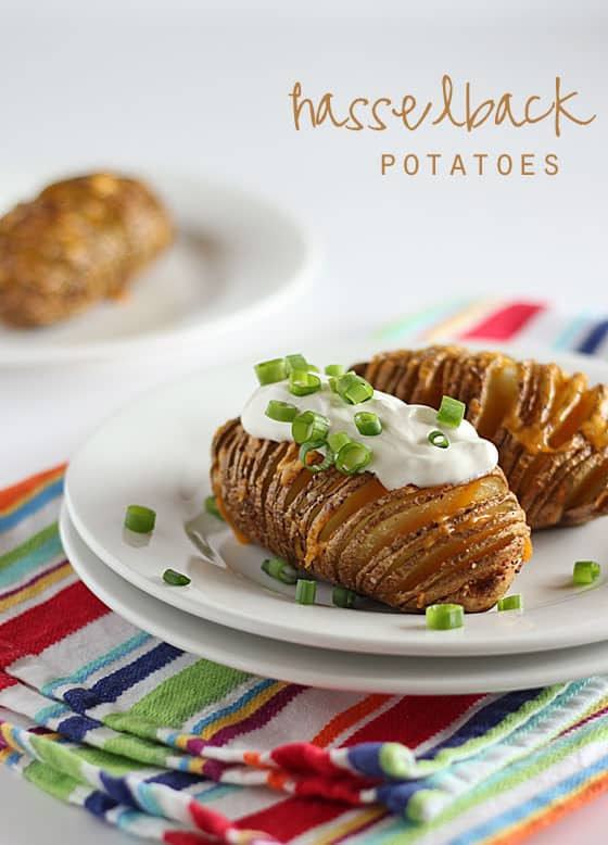 Thinly sliced baked potatoes topped with melted cheese, sour cream and green onions on a white plate.
