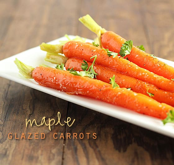 Glazed whole carrots on a white serving dish on a wood surface. Text at bottom left of image.
