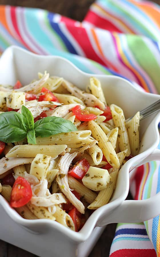 Pasta with chicken, sliced cherry tomatoes, cubed mozzarella and pesto in a white bowl with a spoon.