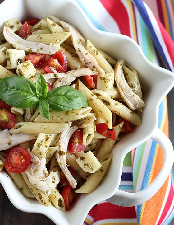 Overhead view of caprese chicken pasta salad garnished with fresh basil in a white square bowl.