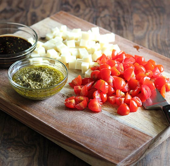 Sliced cherry tomatoes, cubed mozzarella, a bowl of pesto and a bowl of balsamic vinaigrette on a wood cutting board.