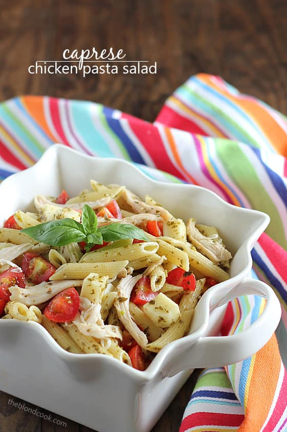 Cooked penne pasta with chicken, tomatoes and pesto in a decorative square white bowl.