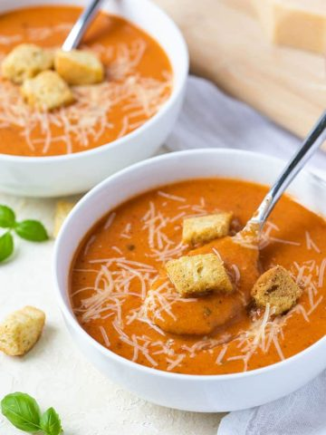A spoon in a white bowl of tomato soup topped with grated Parmesan cheese and croutons.