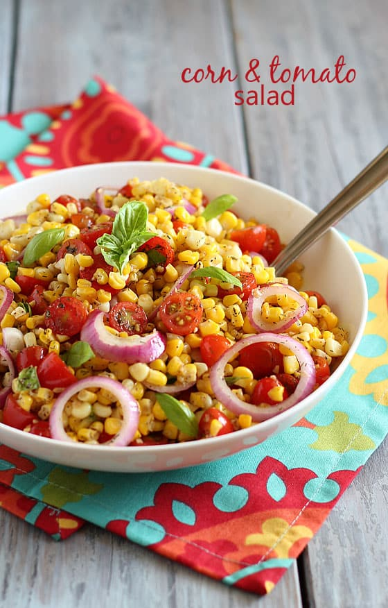 Corn and Tomato Salad in a round white bowl with a serving spoon