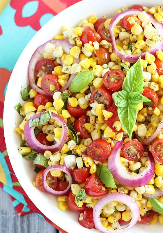 Overhead view of corn and tomato salad in a bowl topped with fresh basil