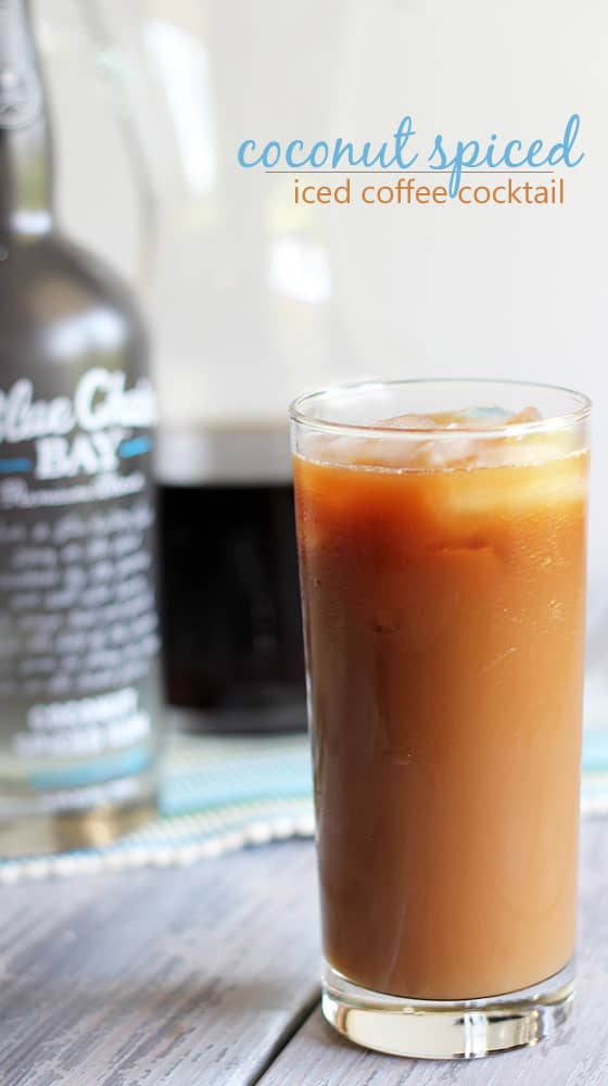 A coffee cocktail in a glass with ice. A bottle of rum and pitcher of coffee is in the background.