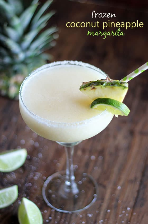 A frozen margarita in a glass garnished with pineapple and lime.