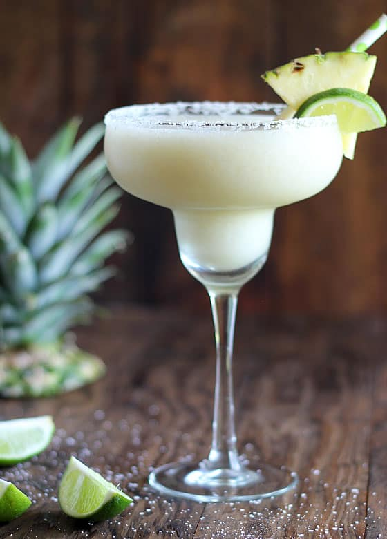 Front view of a glass of frozen margarita on a wood surface.