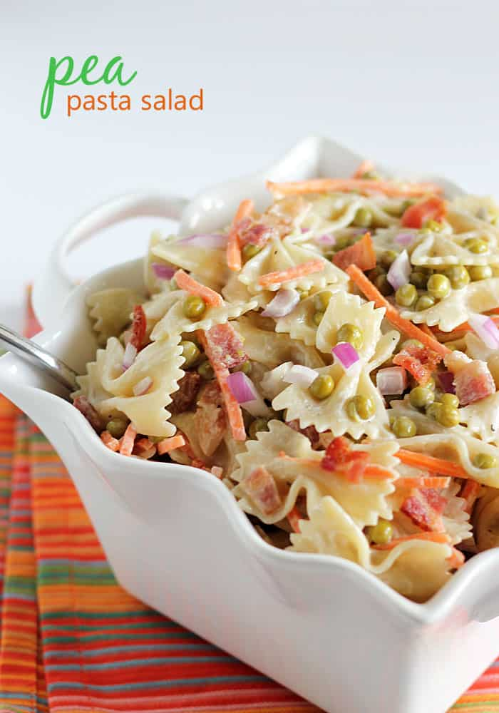 Bow tie pasta with peas, bacon, carrots and red onion in a square white decorative bowl.
