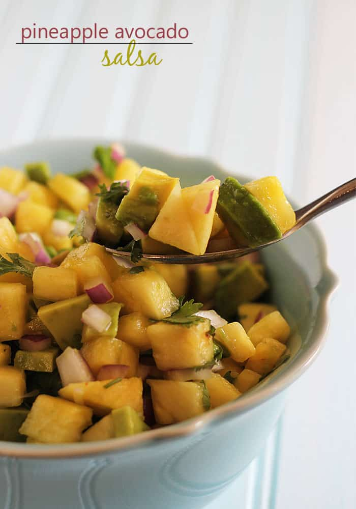 A salsa with pineapple, red onion, avocado and cilantro in a blue bowl with a spoon.