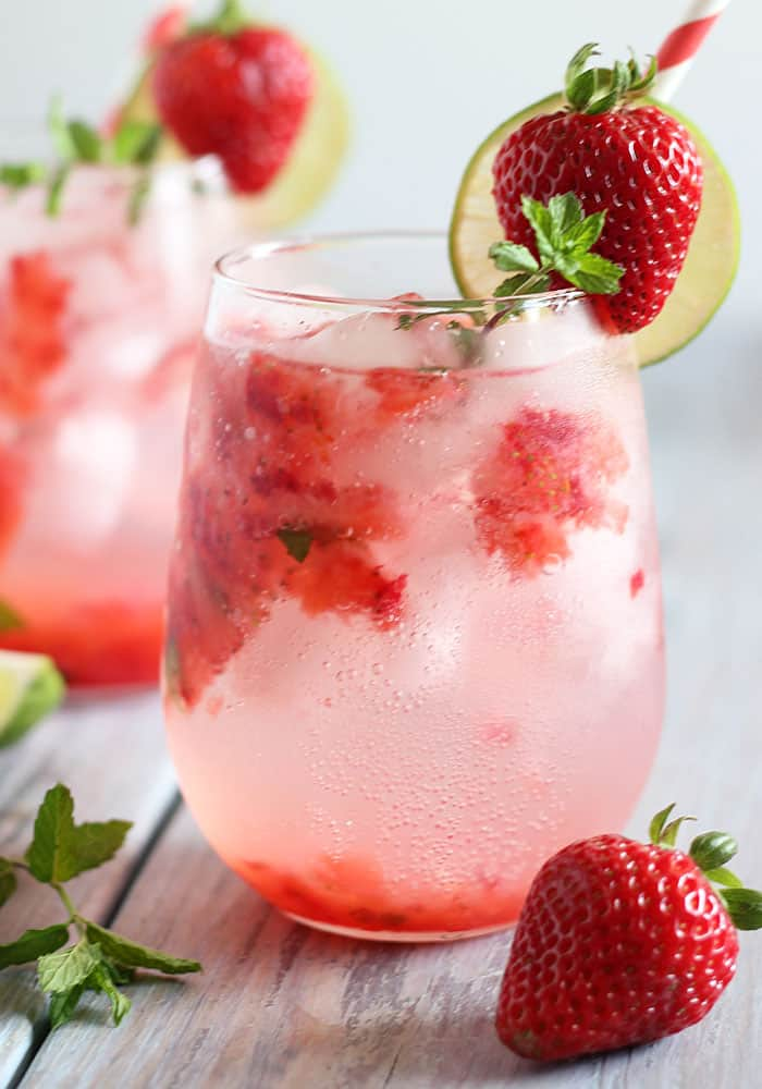 Front closeup view of a mojito in a glass garnished with a fresh strawberry and lime.