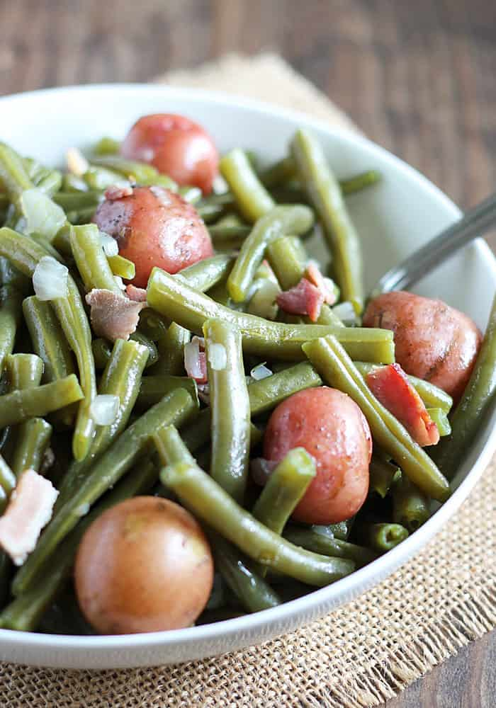 Closeup view of southern style green beans with baby red potatoes, pork pieces and onion in a white bowl.