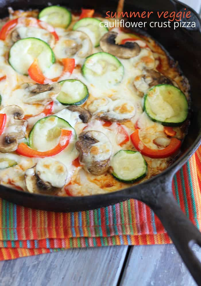 A pizza topped with sliced zucchini, mushrooms, onions and peppers baked in a cast iron skillet.