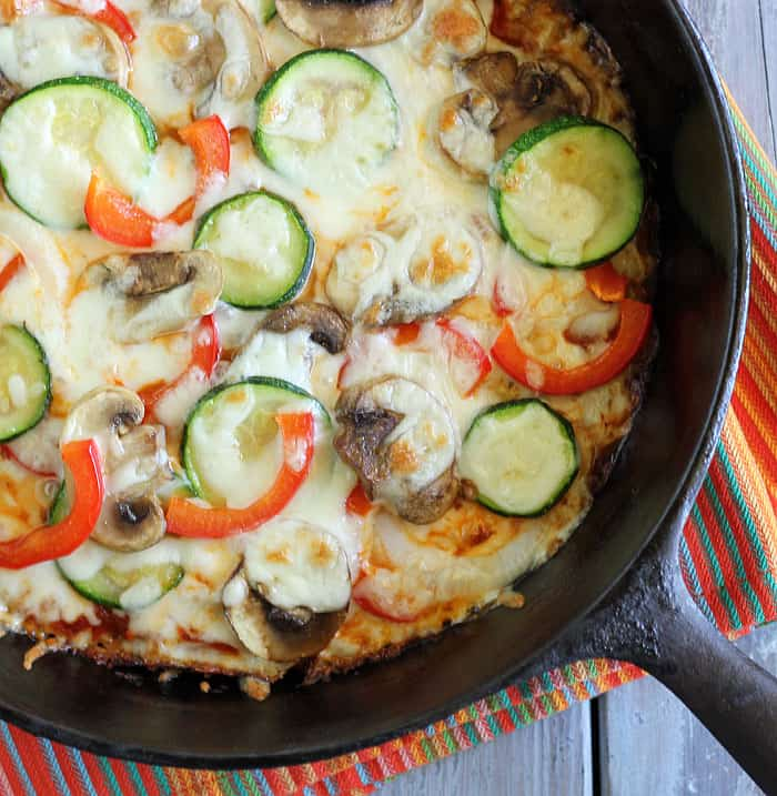 Overhead closeup of a vegetable pizza in a cast iron skillet on a striped napkin.