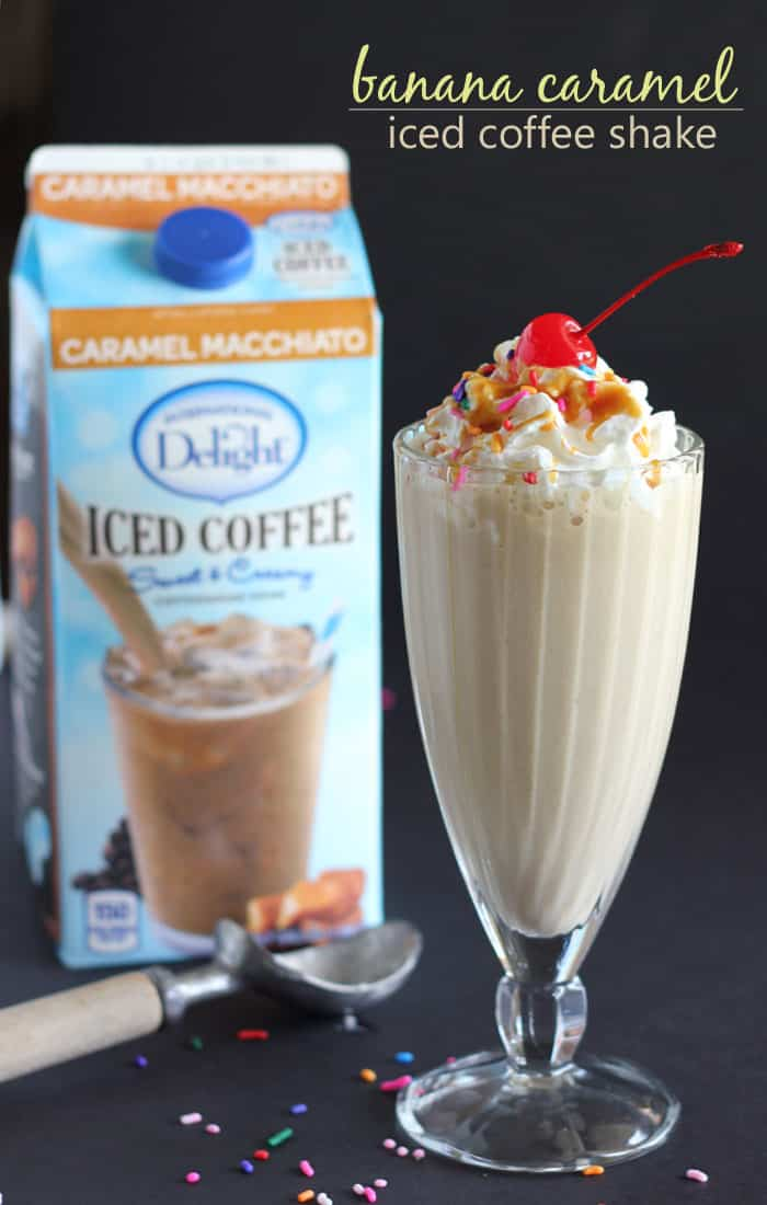 A milkshake topped with whipped cream and a cherry. A carton of iced coffee is in the background.