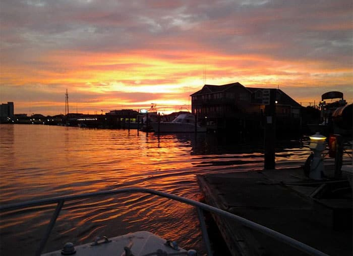 View from the bow of a boat of the waterfront at sunset in Morehead City, NC.
