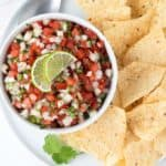 Overhead shot of Pico de Gallo in a round white bowl on a round white plate with tortilla chips.