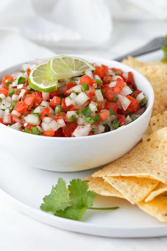 Front view of pico de gallo in a white bowl beside tortilla chips.