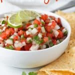 """A white bowl of pico with overlay text that reads """"pico de gallo""""."""