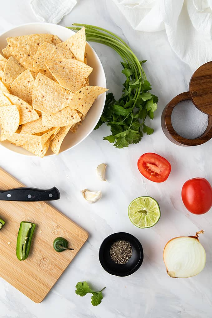 Overhead shot of Pico de Gallo ingredients and a bowl of tortilla chips on a marble white surface.