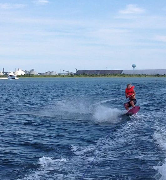 A young woman wearing a life preserver wake boarding on a pink board.