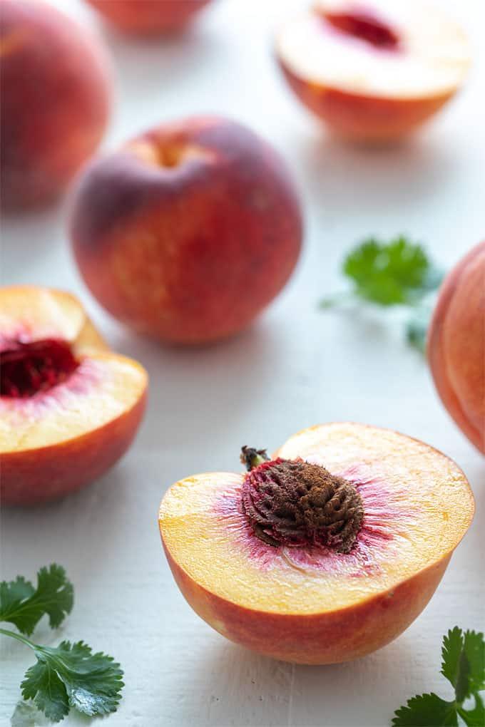A peach sliced in half with whole peaches in the background