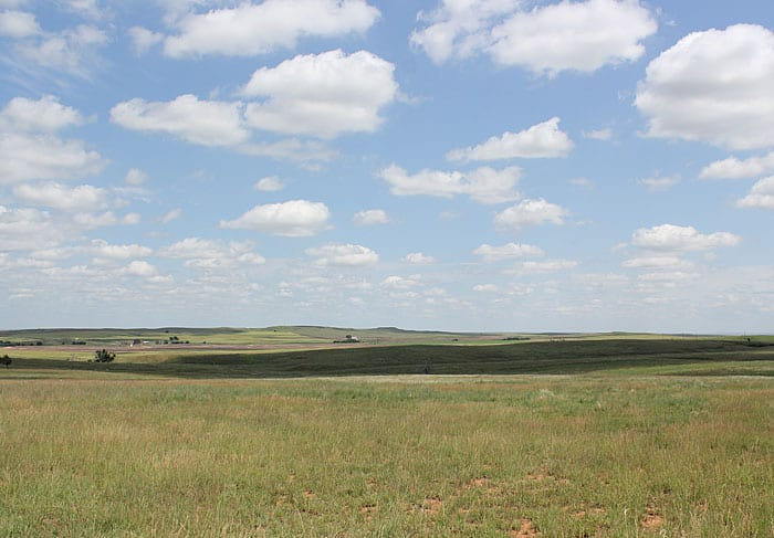 A landscape of grass, hills and blue skies with clouds in Kansas.
