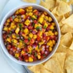 Overhead view of peach salsa in a white bowl on a white plate with tortilla chips